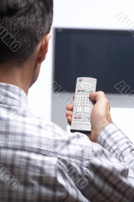 man in front of tv switching channel