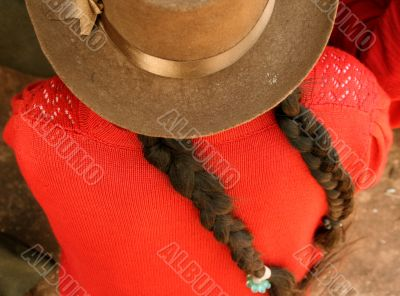 Latina with plaited hair and hat