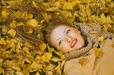 The red-haired woman lays in yellow leaves