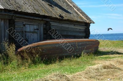 An old shed with a reverse fishing boat on the lake bank