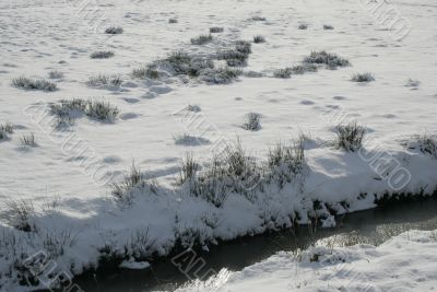 a field of snow and a small stream