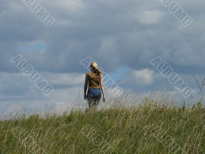 alone female figure in wide field uder cloudy sky