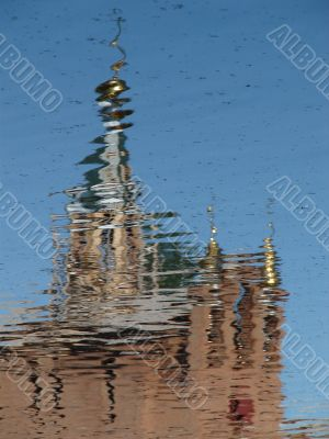 Church Cupola with Cross reflected in wavy water