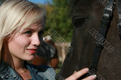 Blond female with brown horse close-up portrait