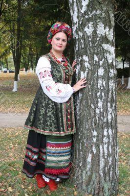 Young lady in Ukrainian costume near birch