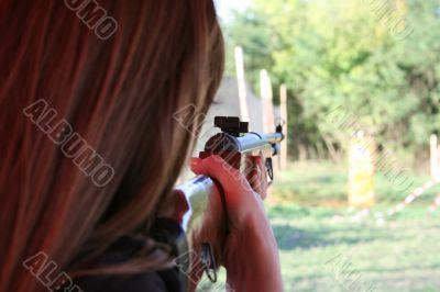 backside wiev of female shooter taking aim
