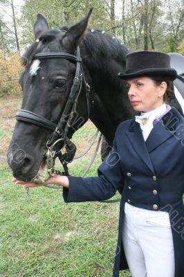 equestrian spotswoman holds black stallion