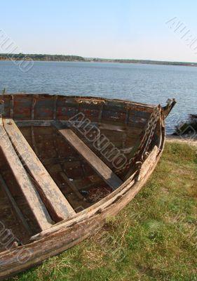 ruined vintage wooden boat on riverside
