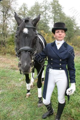 equestrian spotswoman holds black stallion