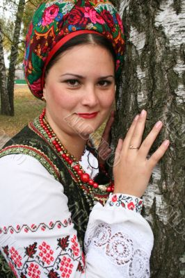 Young lady in Ukrainian costume near birch