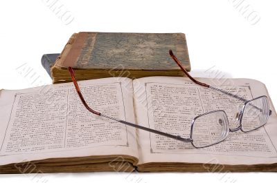 The open ancient book with glasses laying on it on a background