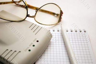 modem, notebook, pen and glasses