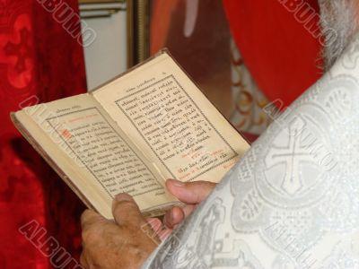 Opened Slavic Gospel in hands of orthodox priest