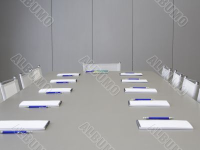 A grey table with grey chairs and notebooks laying