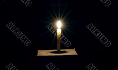 Burning candle on a black background