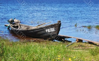 Old wooden fishing motor boat by the lake bank