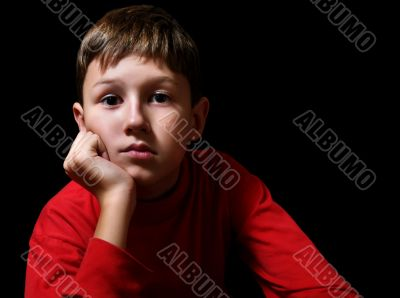 The thoughtful boy in a dark room