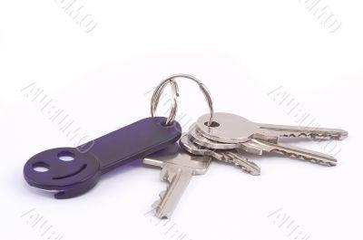 Bunch of keys with dark blue smile trinket.