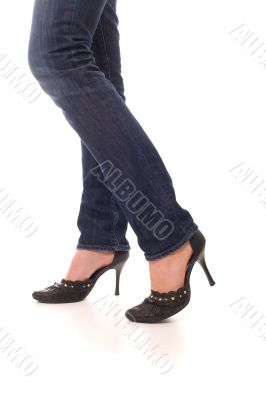 Woman legs dressed in jeans and black shoes walk forward