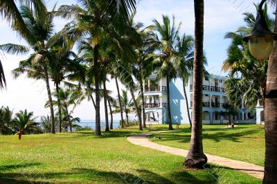 Tropical seaside resort hotel building with palm trees