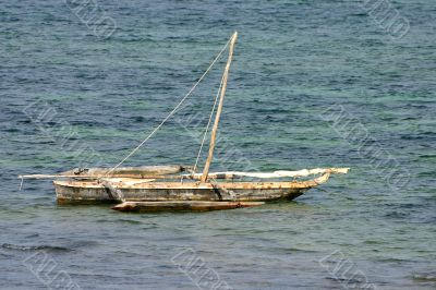 A small wooden boat anchored in the bay
