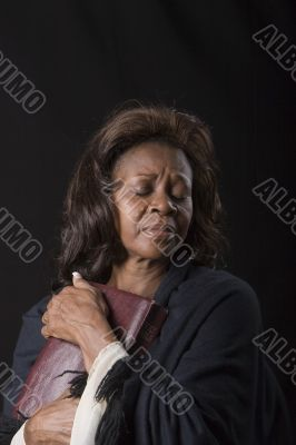 Woman Clutching Bible Eyes Closed