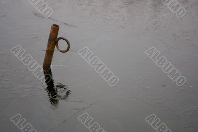 A rusty iron pole in the ice of a small lake