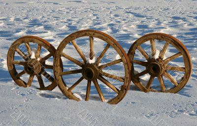 Three wooden wheels in a snow floor.