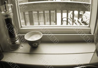 window-sill with paper mill and salt-cellar