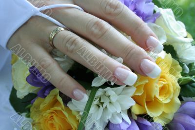 The gentle hand of the bride lays on a bouquet