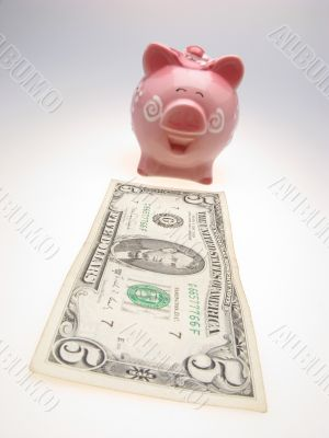 piggy bank and five dollars