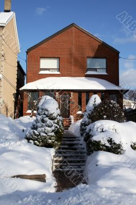 Snowed red-bricked house in downtown Toronto