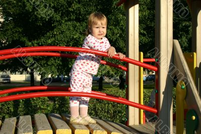 Toddler standing on playground in sunset lights