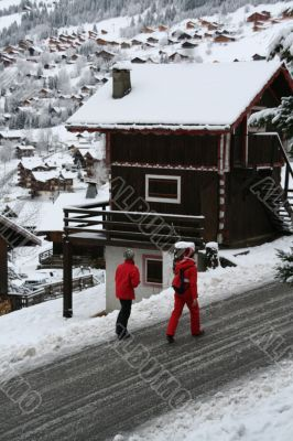 Walkers passing alpine chalet