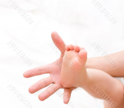 Man hold baby leg on palm