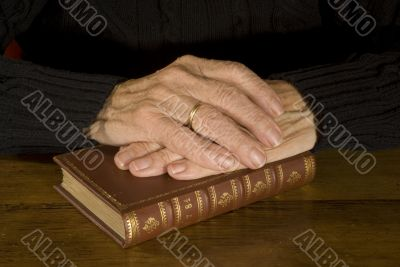 Old hands resting at antique bible
