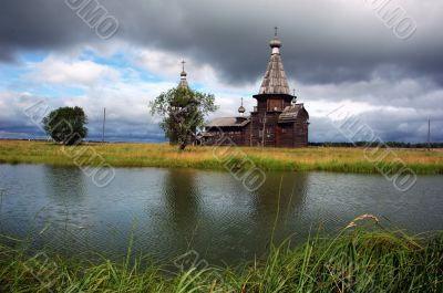 Ancient wooden church beyond the river with stormy sky
