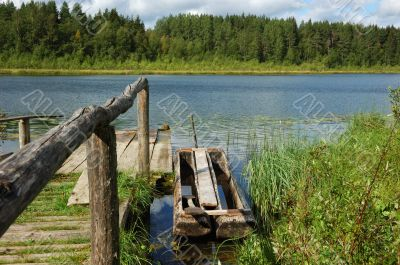 Forest lake with fishing boat at berth
