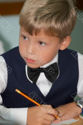 Young boy thinking in classroom