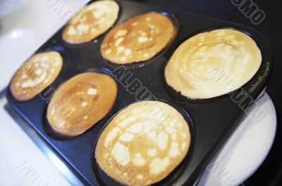 breakfast with six pancakes on electric oven