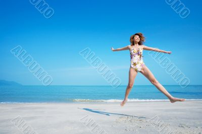 woman jumping happily in swimsuit