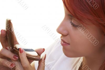 beautician is doing make-up to red-haired woman