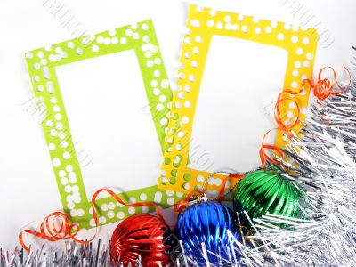 two photoframes with decorative balls and tinsel
