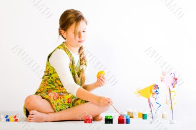 Young girl painting eggs