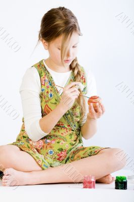 Young girl concentrated on painting eggs for easter