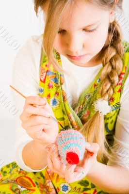 Young girl painting eggs for easter