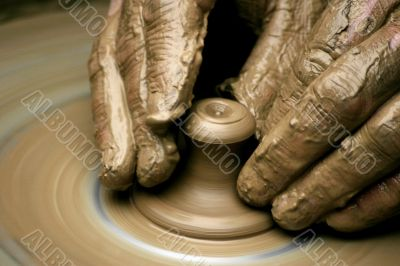 Hands of the potter on potter`s wheel