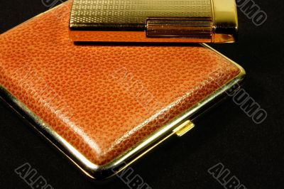 cigarette-case and lighter on black background