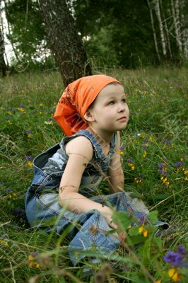 little girl sit on grass in forest