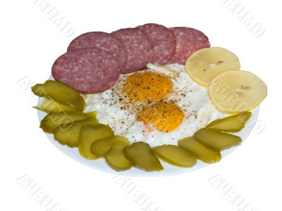 Fried eggs with salami, lemon and pickles